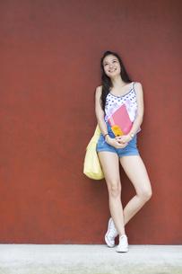 赤い壁の前で微笑む女子学生のポートレートの写真素材 [FYI02972226]