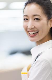 オフィスで笑顔で振り向くビジネス女性の写真素材 [FYI02972231]