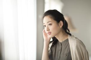 窓際で遠くを眺める女性の写真素材 [FYI02972234]