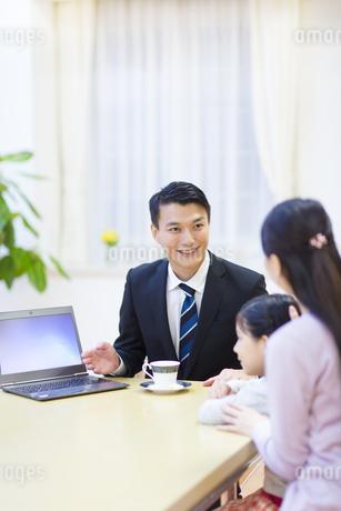 説明する訪問営業の男性と話を聞く母と娘の写真素材 [FYI02972237]