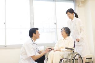 車椅子の患者に添う男性医師と女性看護師の写真素材 [FYI02972238]