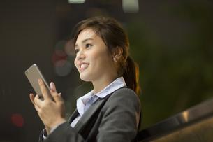 夜の街を背景にスマートフォンを持ち上を見上げるビジネス女性の写真素材 [FYI02972242]