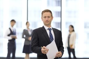オフィスビルのロビーで資料を持って立つビジネス男性の写真素材 [FYI02972246]