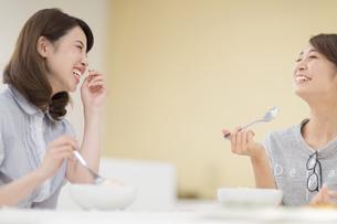 食事をしながら笑い合う2人の女性の写真素材 [FYI02972248]