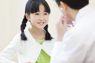 男性医師に問診されている女の子の写真素材 [FYI02972250]