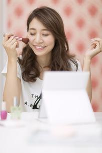 鏡の前でメイクアップをする女性の写真素材 [FYI02972252]