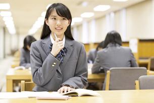 図書室で勉強中に顔を上げる女子高校生の写真素材 [FYI02972253]
