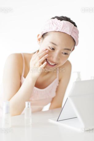 卓上ミラーでスキンケアをする微笑む女性の写真素材 [FYI02972254]