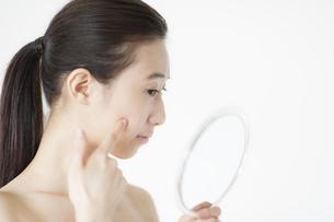 手鏡を見て微笑む女性の写真素材 [FYI02972258]