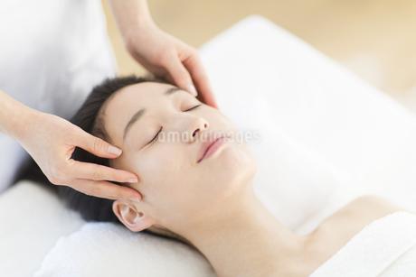 仰向けで顔をマッサージされている女性の写真素材 [FYI02972264]