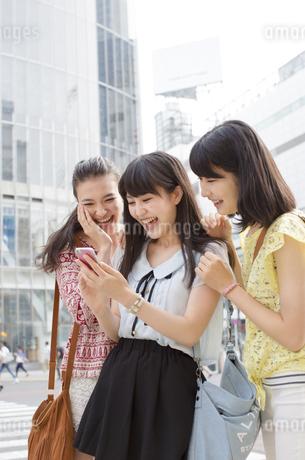 スマートフォンを見つめて喜ぶ3人の若い女性の写真素材 [FYI02972268]