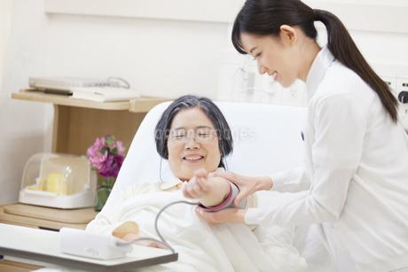 ベッドの患者に血圧計をつける女性看護師の写真素材 [FYI02972279]