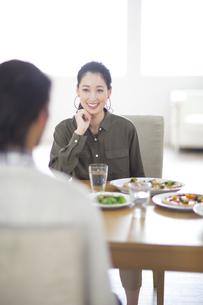 ダイニングテーブルで食事を楽しむ男性と女性の写真素材 [FYI02972297]