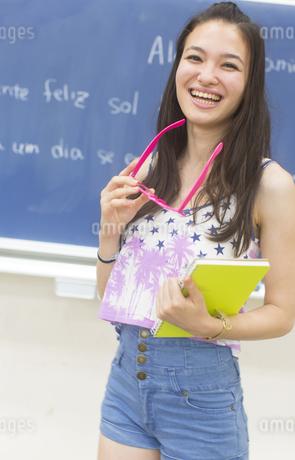 黒板の前で眼鏡を持って笑う女子学生のポートレートの写真素材 [FYI02972299]