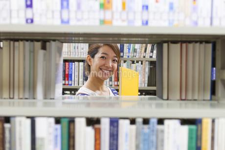 図書室で本の間から覗く女子学生の写真素材 [FYI02972301]