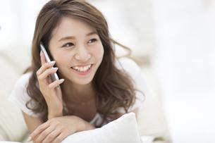 ソファの上で電話をかける女性の写真素材 [FYI02972303]