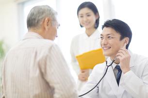 患者に聴診器をあてる男性医師の写真素材 [FYI02972307]