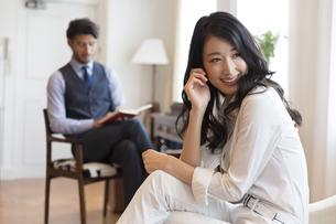 ソファーに座って微笑む女性と椅子に座って本を読む男性の写真素材 [FYI02972308]
