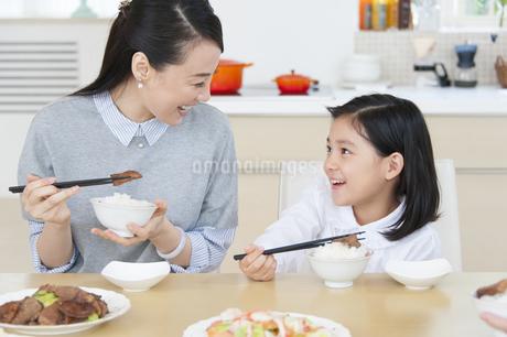 食事中に顔を見合わせて笑う母と娘の写真素材 [FYI02972309]