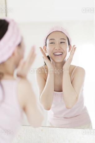鏡の前でスキンケアをする微笑む女性の写真素材 [FYI02972316]