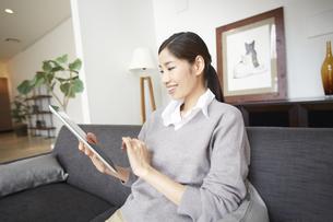 ソファーでスマートデバイスを見て微笑む女性の写真素材 [FYI02972317]