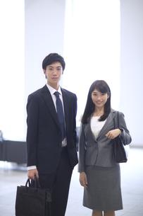 オフィスビルのロビーで立つビジネス男女の写真素材 [FYI02972323]