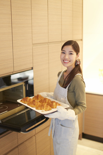 焼いたクロワッサンを持った主婦のスナップの写真素材 [FYI02972325]