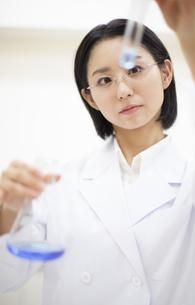 フラスコと試験管を使って研究をしている女性研究員の写真素材 [FYI02972330]