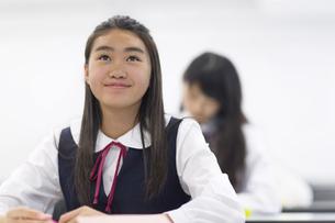 教室で上を見上げ微笑む女子学生の写真素材 [FYI02972335]