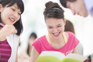 ノートを見て笑う学生たちの写真素材 [FYI02972338]