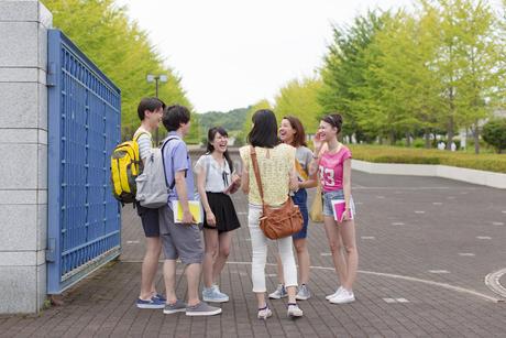 キャンパスの門で笑い合う学生たちの写真素材 [FYI02972342]