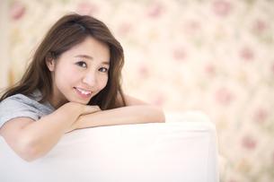 ソファに寄り掛かって微笑む女性のポートレートの写真素材 [FYI02972343]