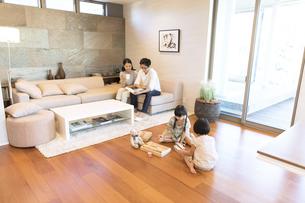 リビングで本を見る夫婦と床で遊ぶ姉妹の写真素材 [FYI02972347]