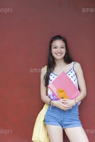赤い壁の前で微笑む女子学生のポートレートの写真素材 [FYI02972350]