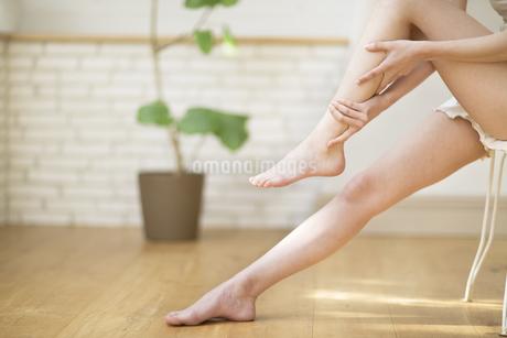 脚のふくらはぎをマッサージをする女性の手元の写真素材 [FYI02972351]