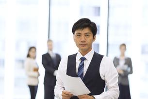 オフィスビルのロビーで資料を持って立つビジネス男性の写真素材 [FYI02972354]
