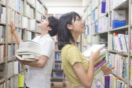 図書室で本を探す男女の学生の写真素材 [FYI02972371]