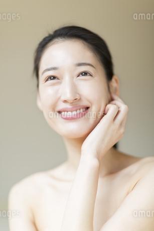 頬に片手を添えて微笑む女性の写真素材 [FYI02972372]