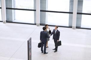 オフィスビルのエントランスで立って握手をするビジネス男女の写真素材 [FYI02972380]