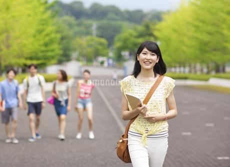 微笑みながらキャンパスを歩く女子学生の写真素材 [FYI02972381]