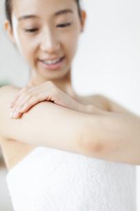 腕をマッサージする微笑む女性の写真素材 [FYI02972383]