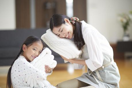 バスタオルに顔を寄せて微笑む親子の写真素材 [FYI02972390]