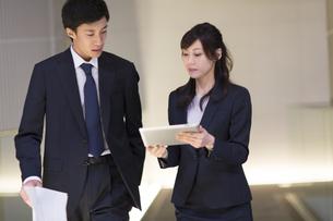 歩きながら打ち合せをするビジネス男女の写真素材 [FYI02972395]