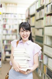 図書室で重ねた本を持って微笑む女子学生の写真素材 [FYI02972402]