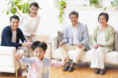 走る子供を見て笑う家族の写真素材 [FYI02972403]