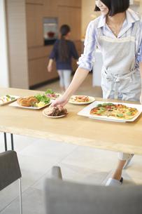 テーブルに食事を用意する親子の写真素材 [FYI02972411]