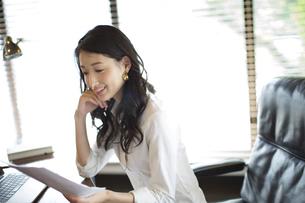 オフィスのデスクの椅子に座って資料を見るビジネス女性の写真素材 [FYI02972416]