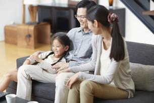 ソファーでくつろぐ3人家族の写真素材 [FYI02972422]