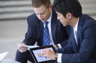 タブレットPCを持ち打ち合せをする2人のビジネス男性の写真素材 [FYI02972423]
