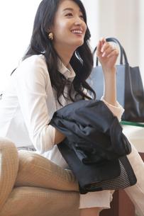 ソファーに座って笑う女性の写真素材 [FYI02972429]